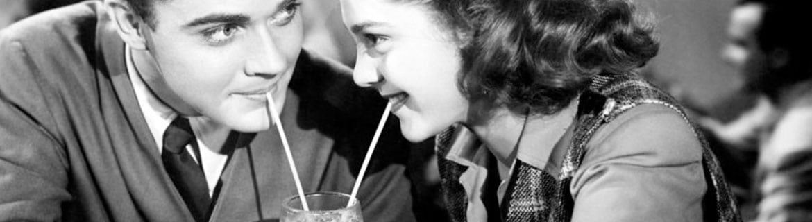 Black and white image from the 50's with a man and woman sharing a milk shake with 2 straws
