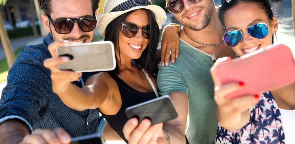 Group of millennials in sunglasses all holding up smart phones to take a selfie