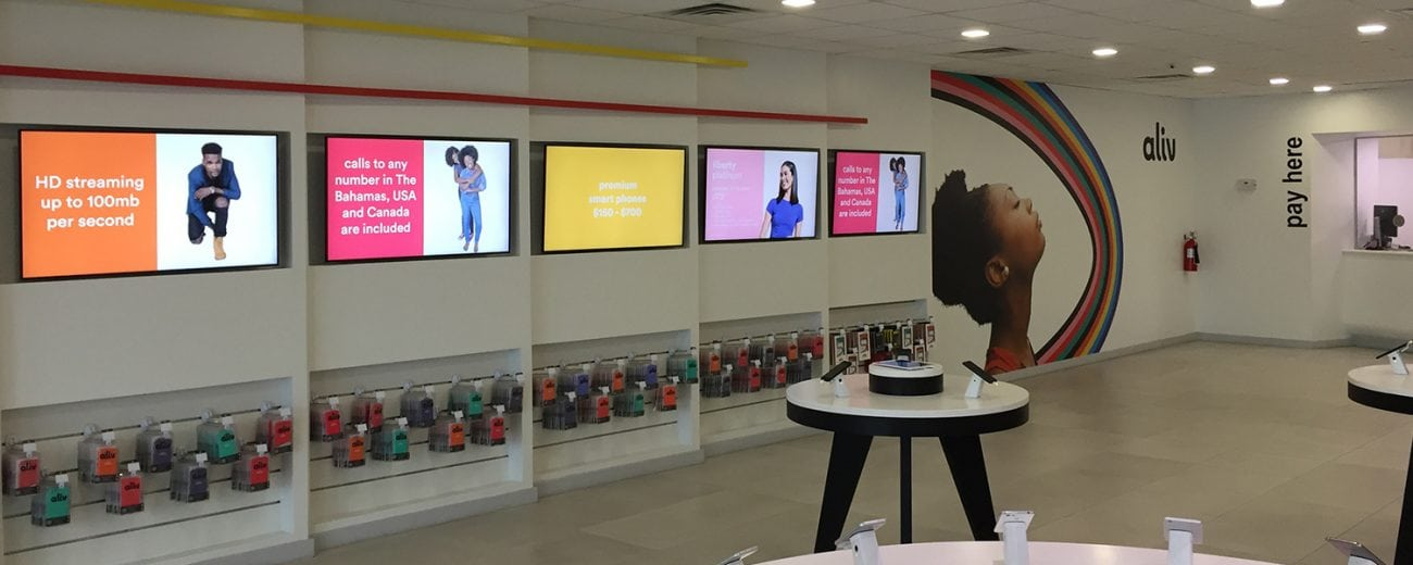 Indie of an Aliv store in Bahamas featuring a wall of screens with advertising