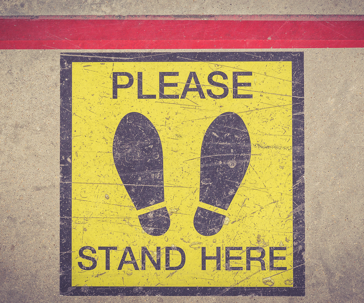 """""""Please Stand Here"""" sign on a floor."""
