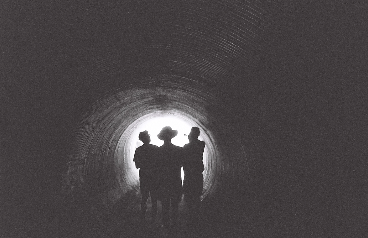 sillouette of 3 boys in a tunnel