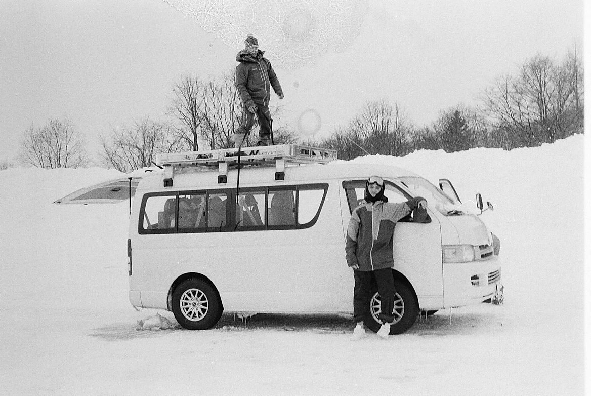 van in the snow in japan in black and white