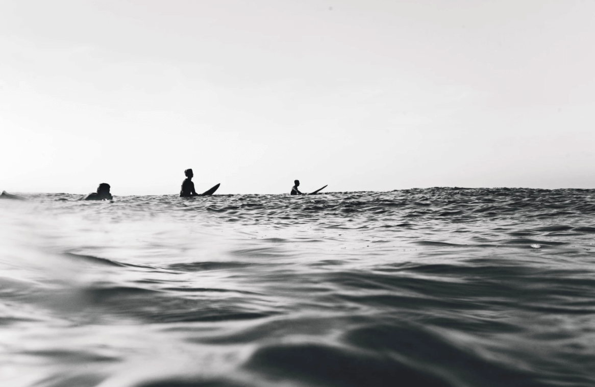 surfing in the ocean in black and white