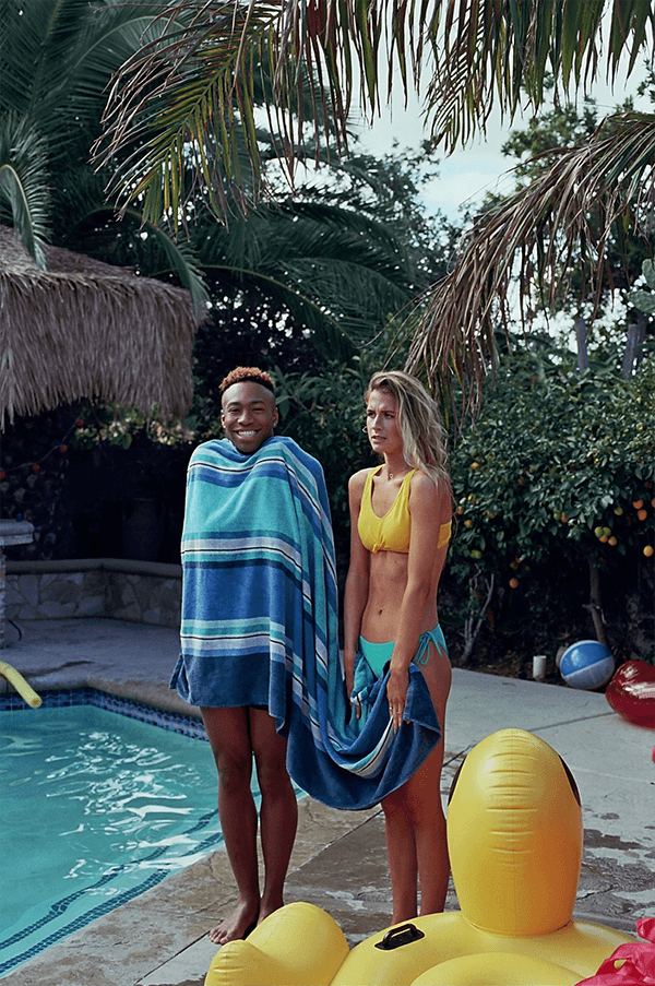 two people standing by a pool