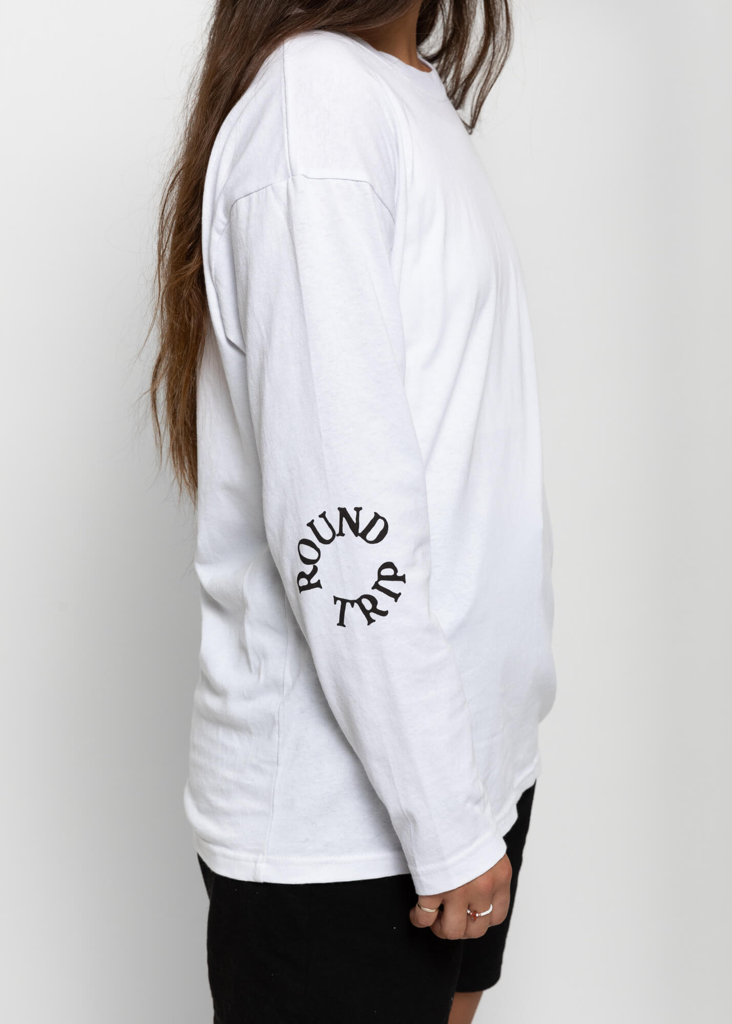 side view of a female model wearing the white round trip longsleeve with the logo on the elbow