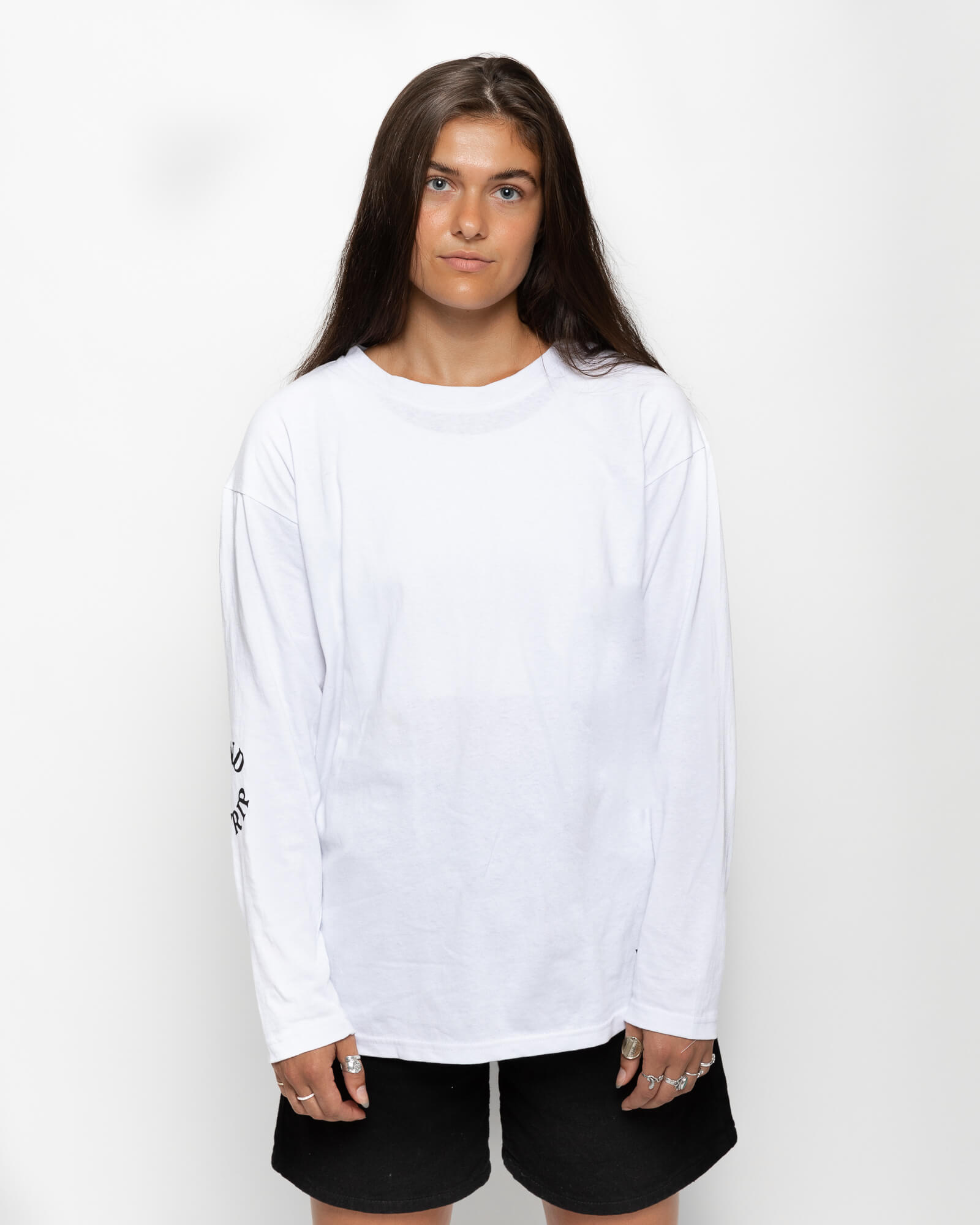 front view of a female model wearing the white round trip longsleeve with black shorts
