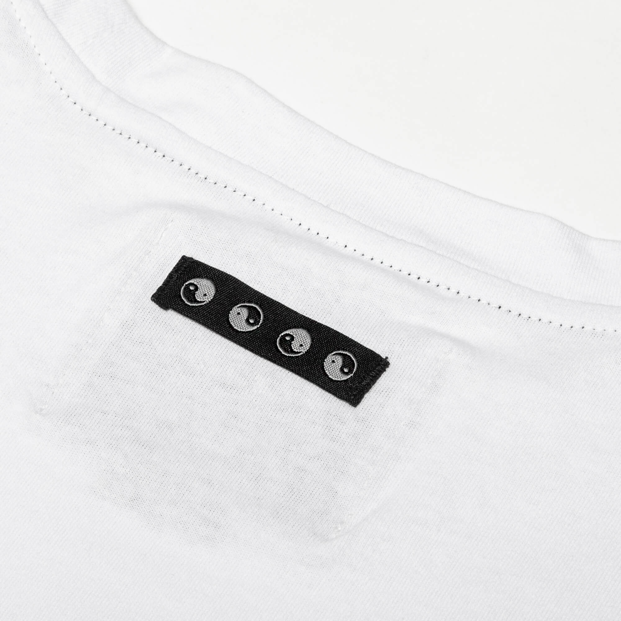 close up of the black collar tag of the white round trip longsleeve