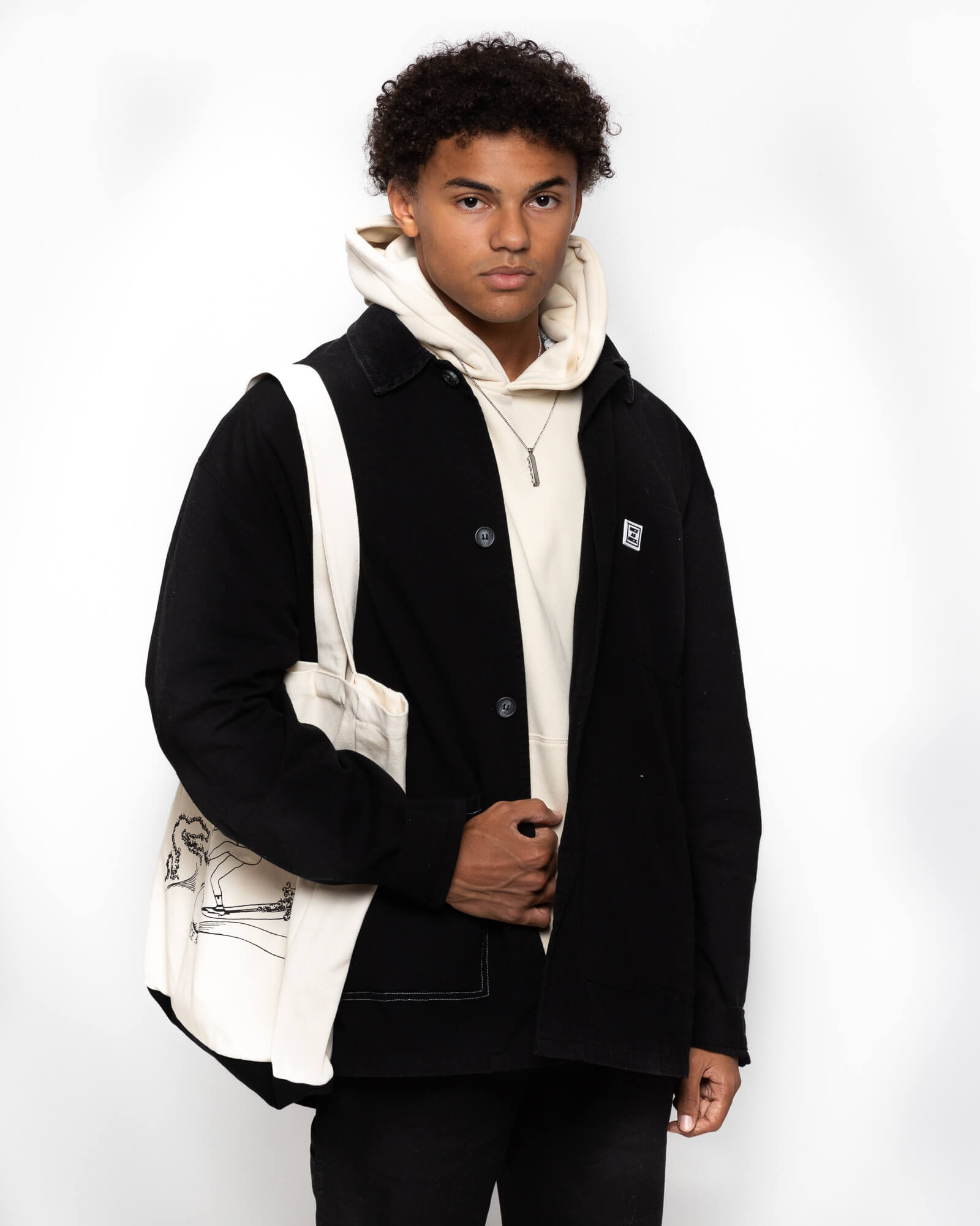 front view of a male model wearing the black kickback jacket with the beige goin' steady hoodie and the white tote bag
