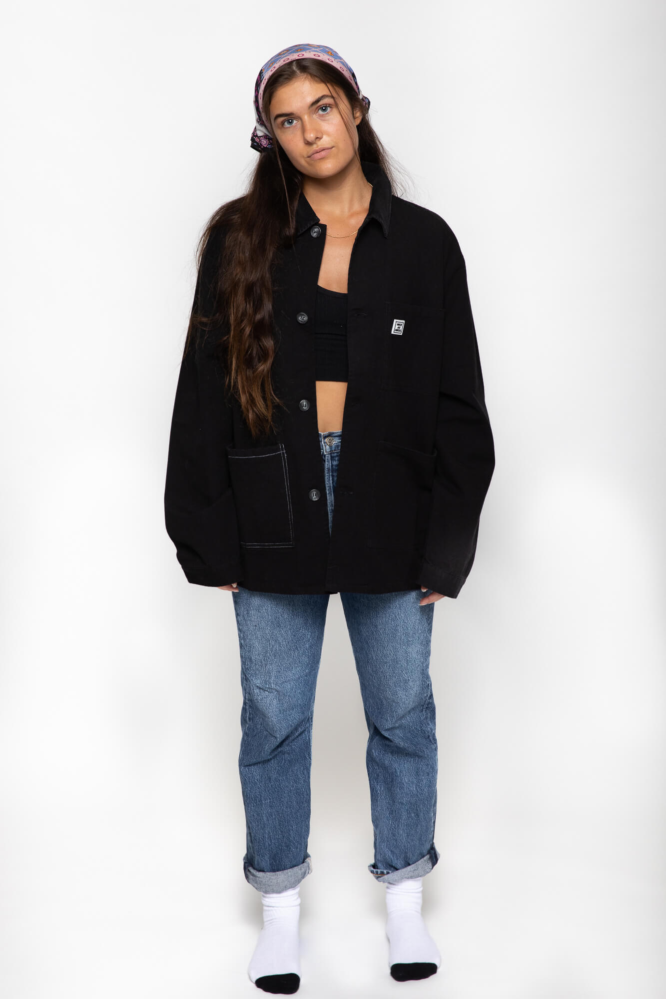 front view of a female model wearing the black kickback jacket with blue jeans and white shoes
