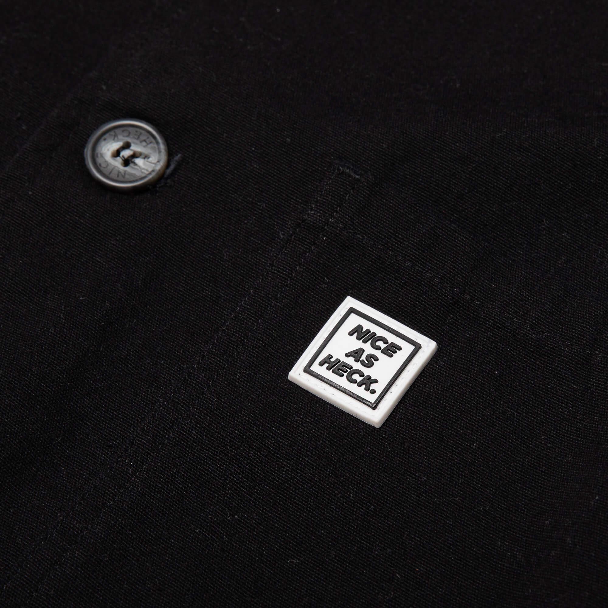 close up of the nice as heck logo on the black kickback jacket