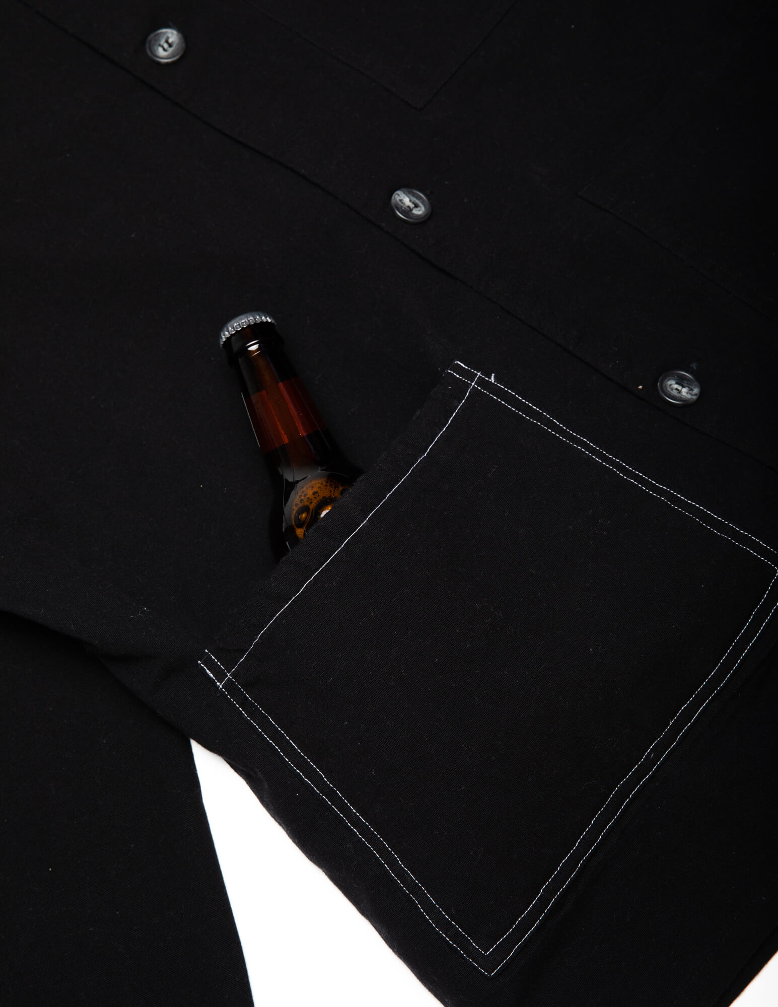 close up of a beer in the insulated drink pocket of the black kickback jacket