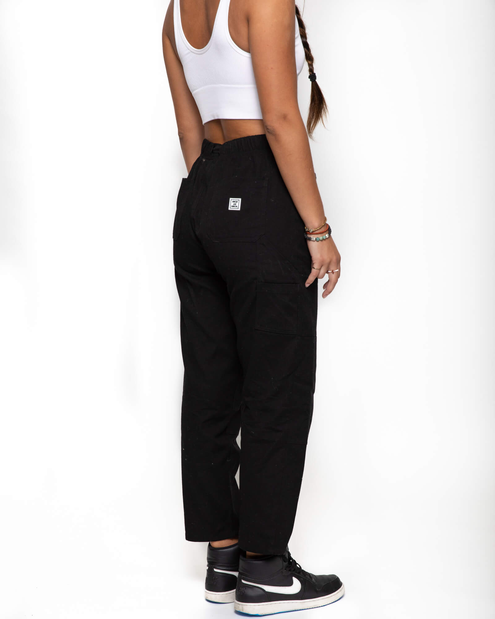 Side view of a female model wearing the black wood worker pants with a white tank top
