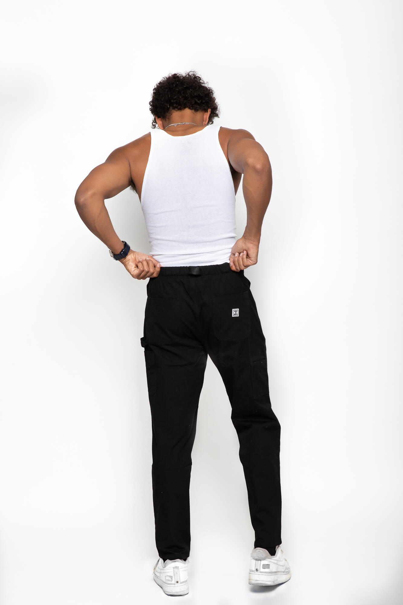 back view of a male model wearing the black wood worker pants with a white tank top
