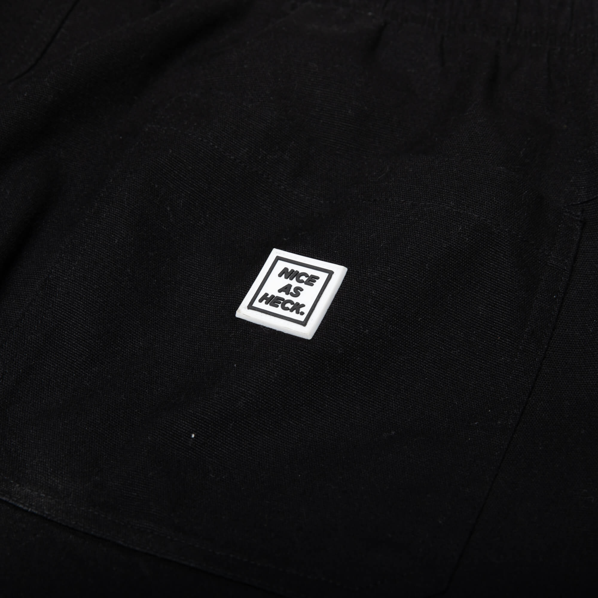 Close up photo of the white logo on the black wood worker pants