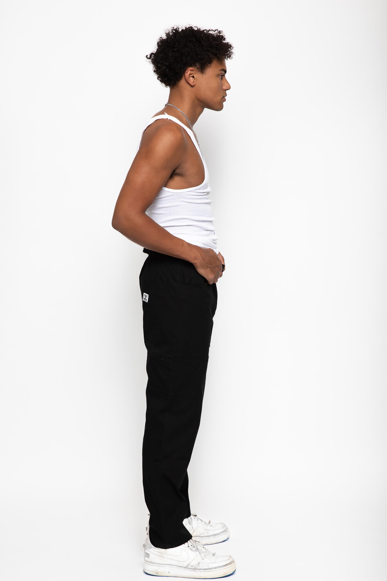 Side view of a male model wearing the black wood worker pants with a white tank top