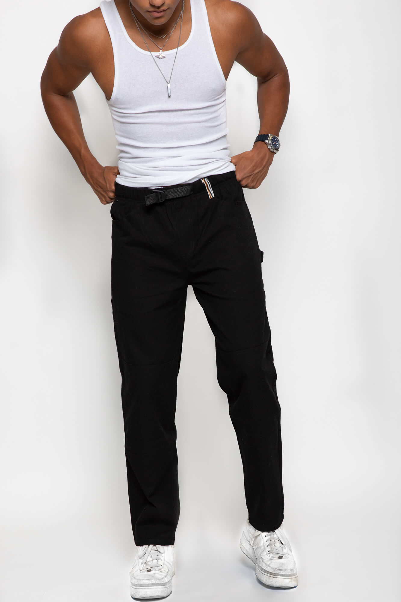 front view of a male model wearing the black wood worker pants with a white tank top