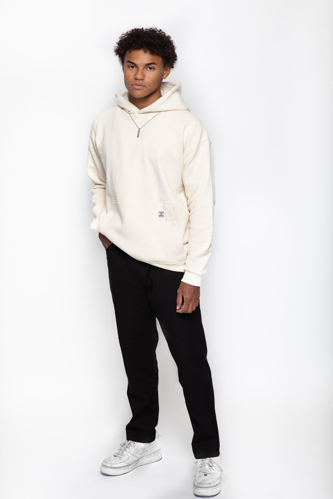 front view of a male model wearing the beige goin steady hoodie and blank pants