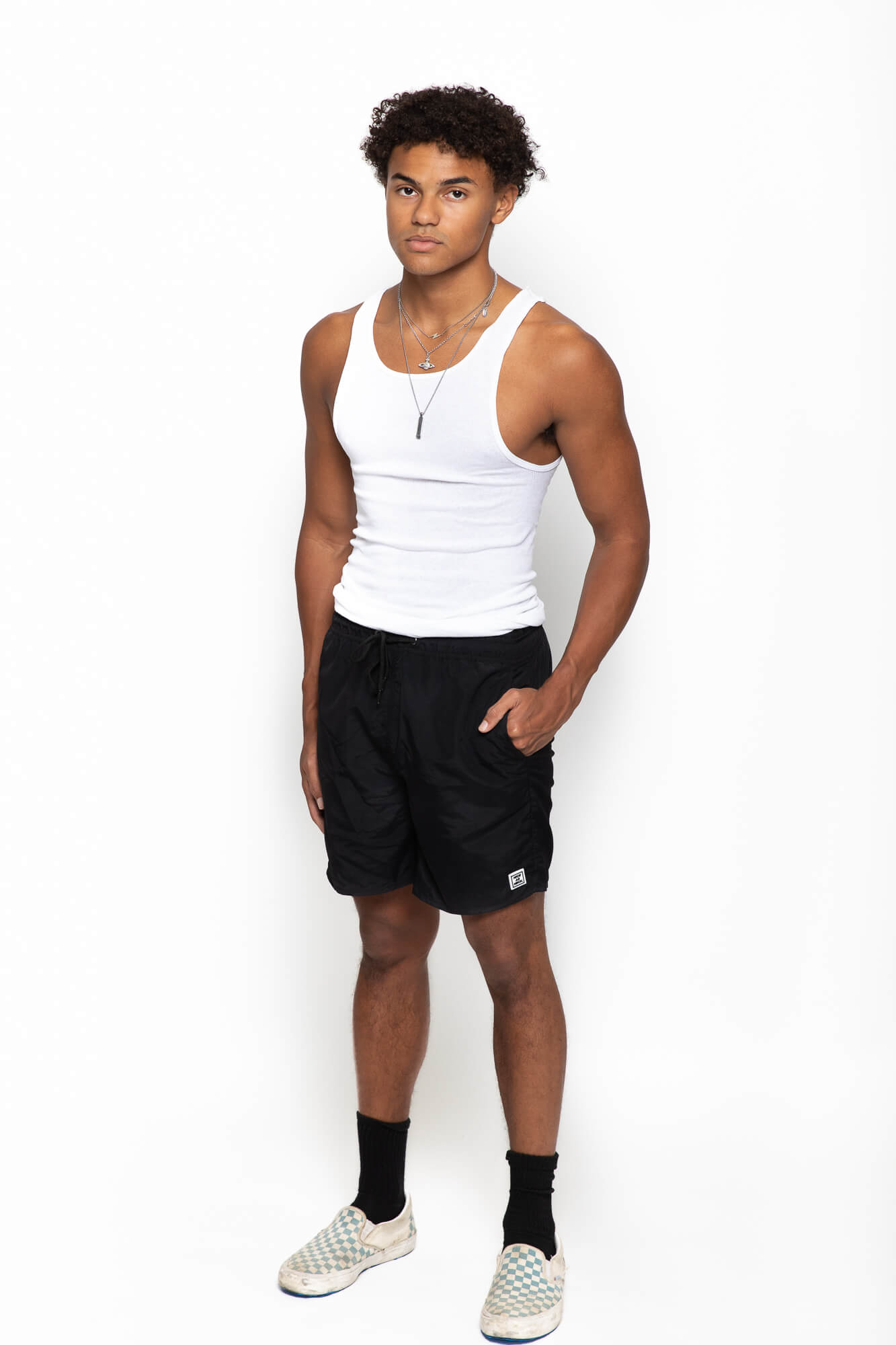 side front view of a male model wearing the twilight nylon shorts with a blue pocket on the back
