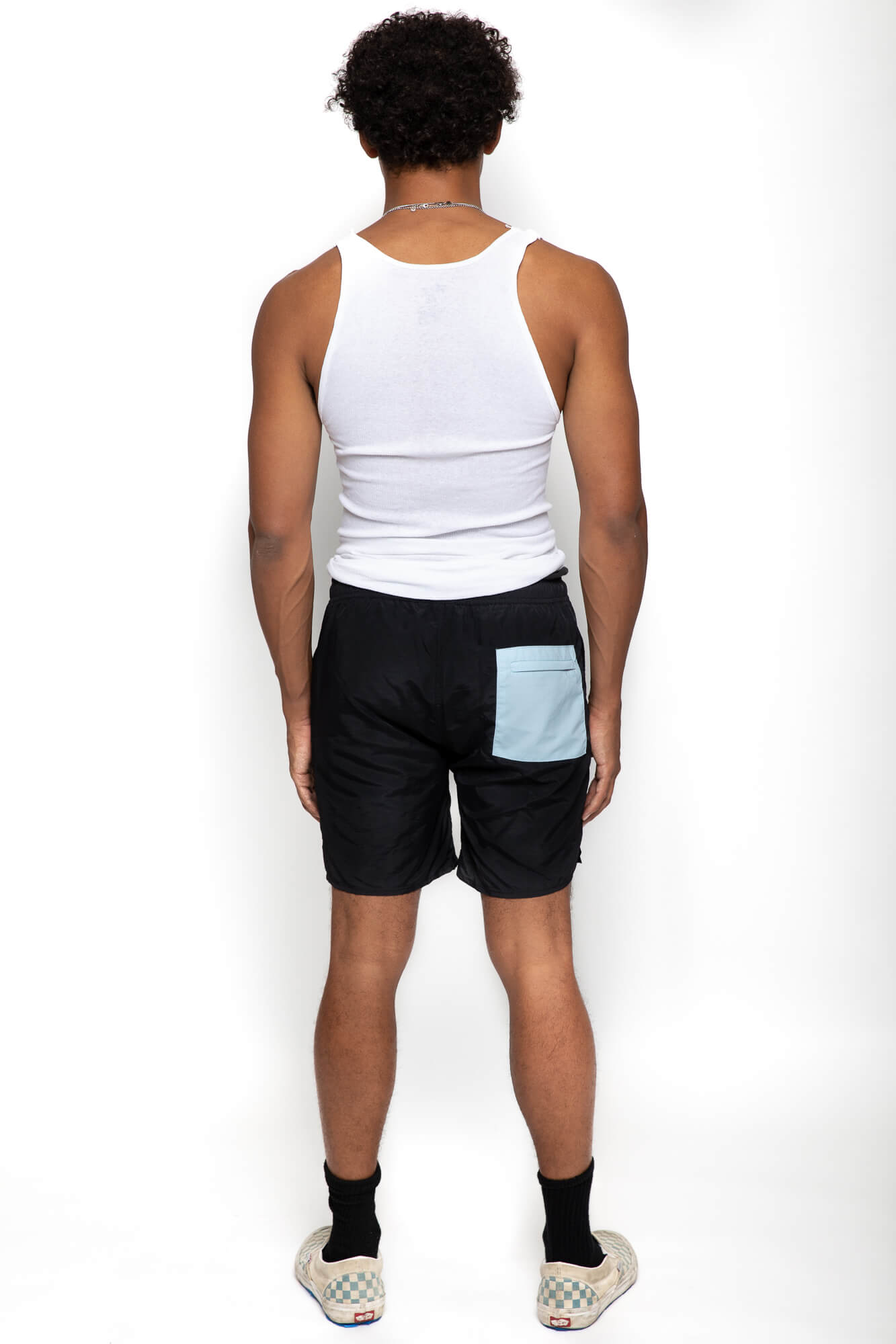 back view of a male model wearing the twilight nylon shorts with a blue pocket on the back
