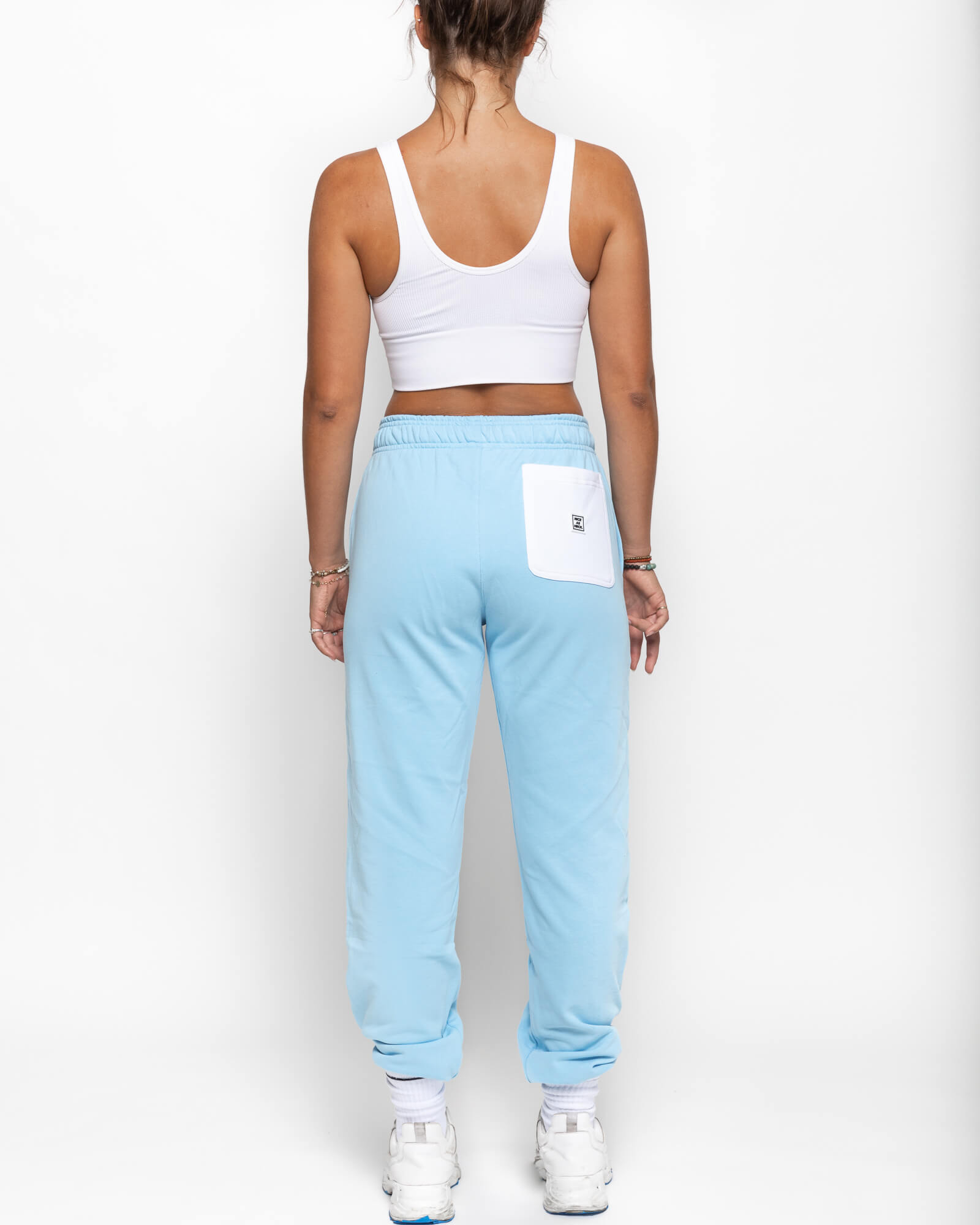 back view of a female model wearing the blue sunday sweats with a white tank top