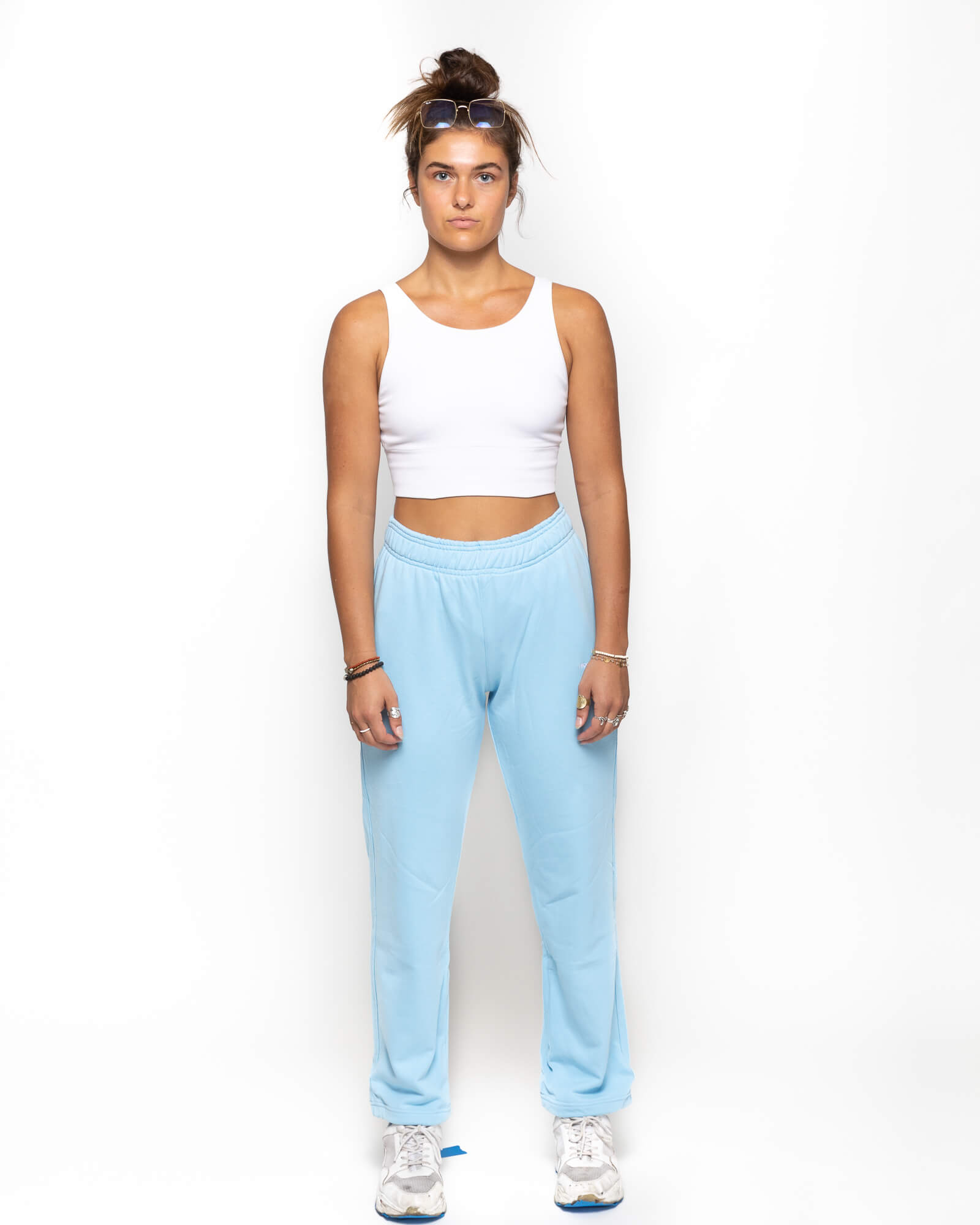 front view of a female model wearing the blue sunday sweats with a white tank top