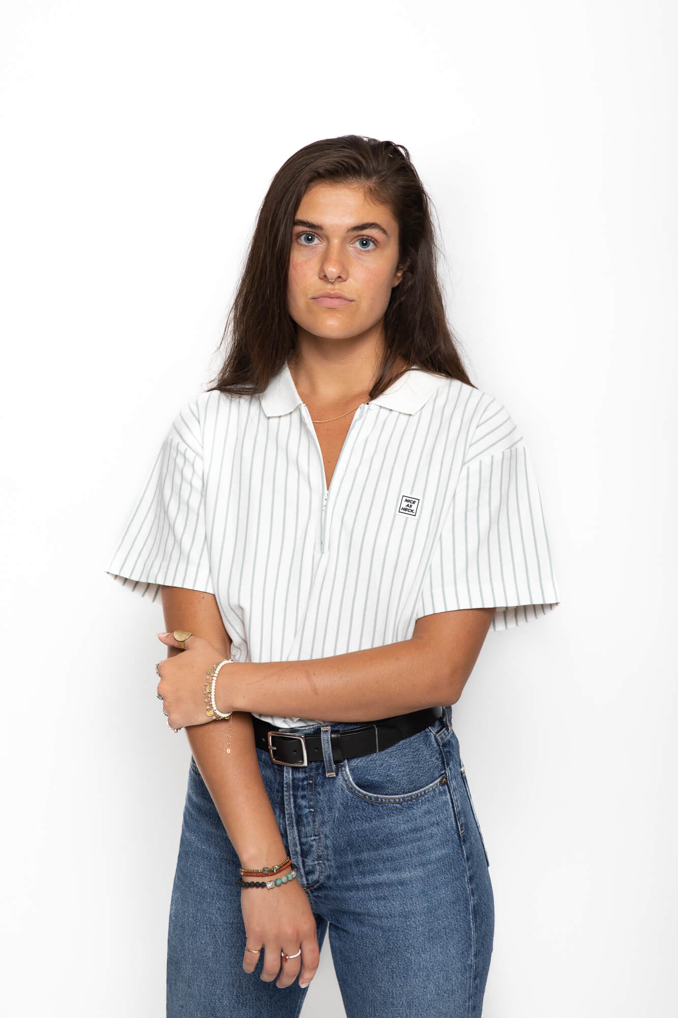 front view of female model holding her arm wearing the d plus polo