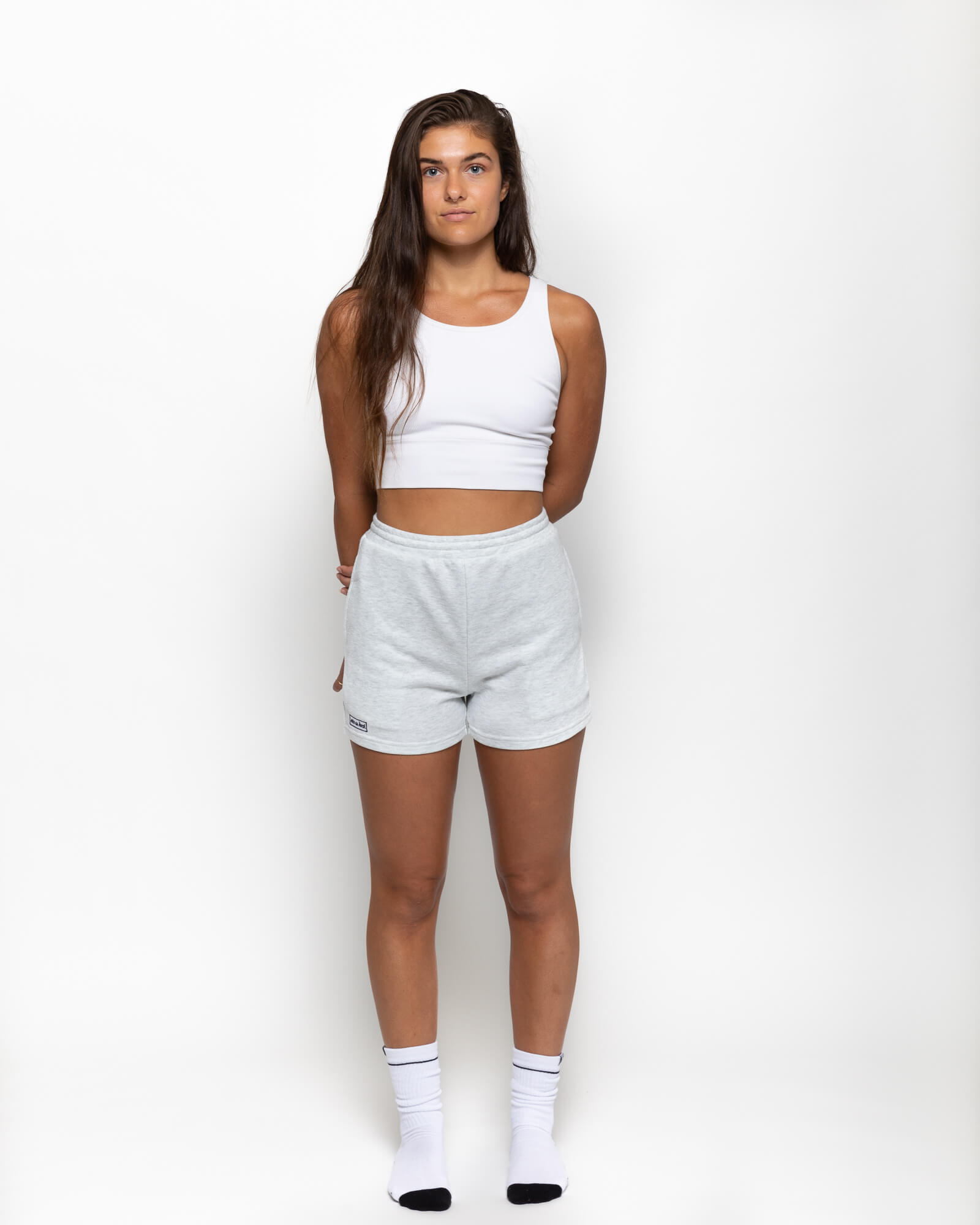 front view of a girl wearing the shorts in a white tank top and white socks
