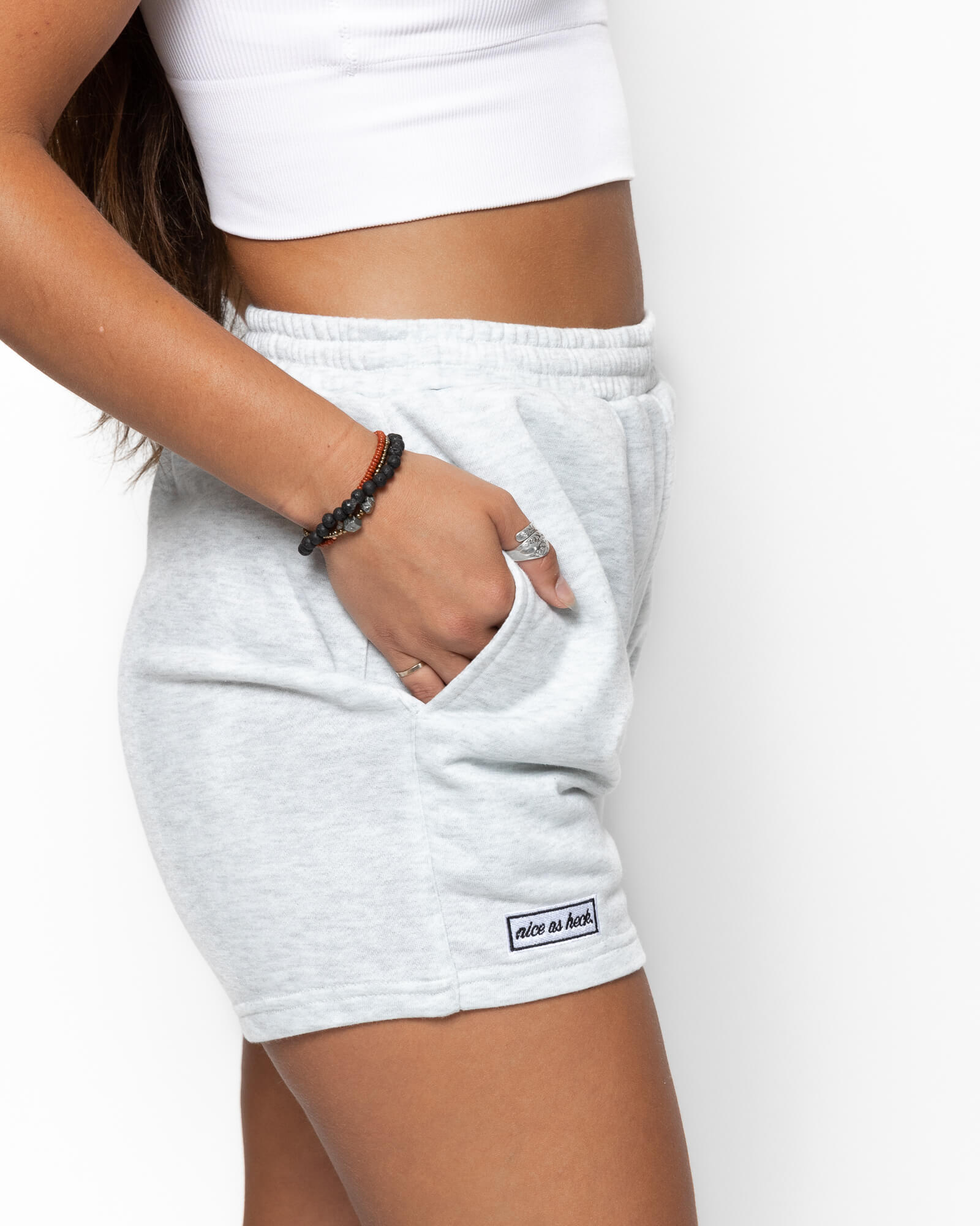 close up side view of a girl wearing the shorts with her hands in her pockets