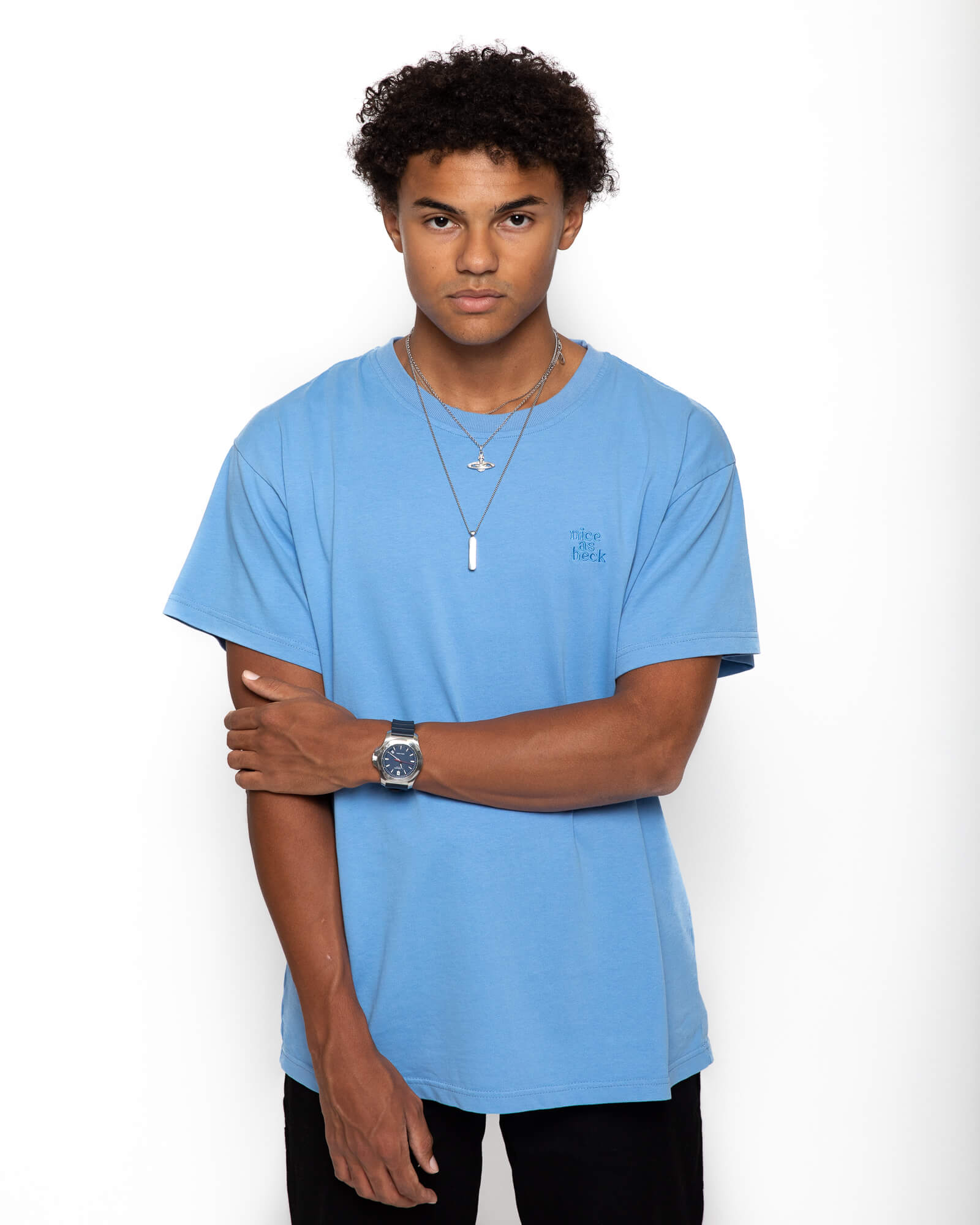 male model wearing the blue weekender tee and grabbing his right arm with his left arm