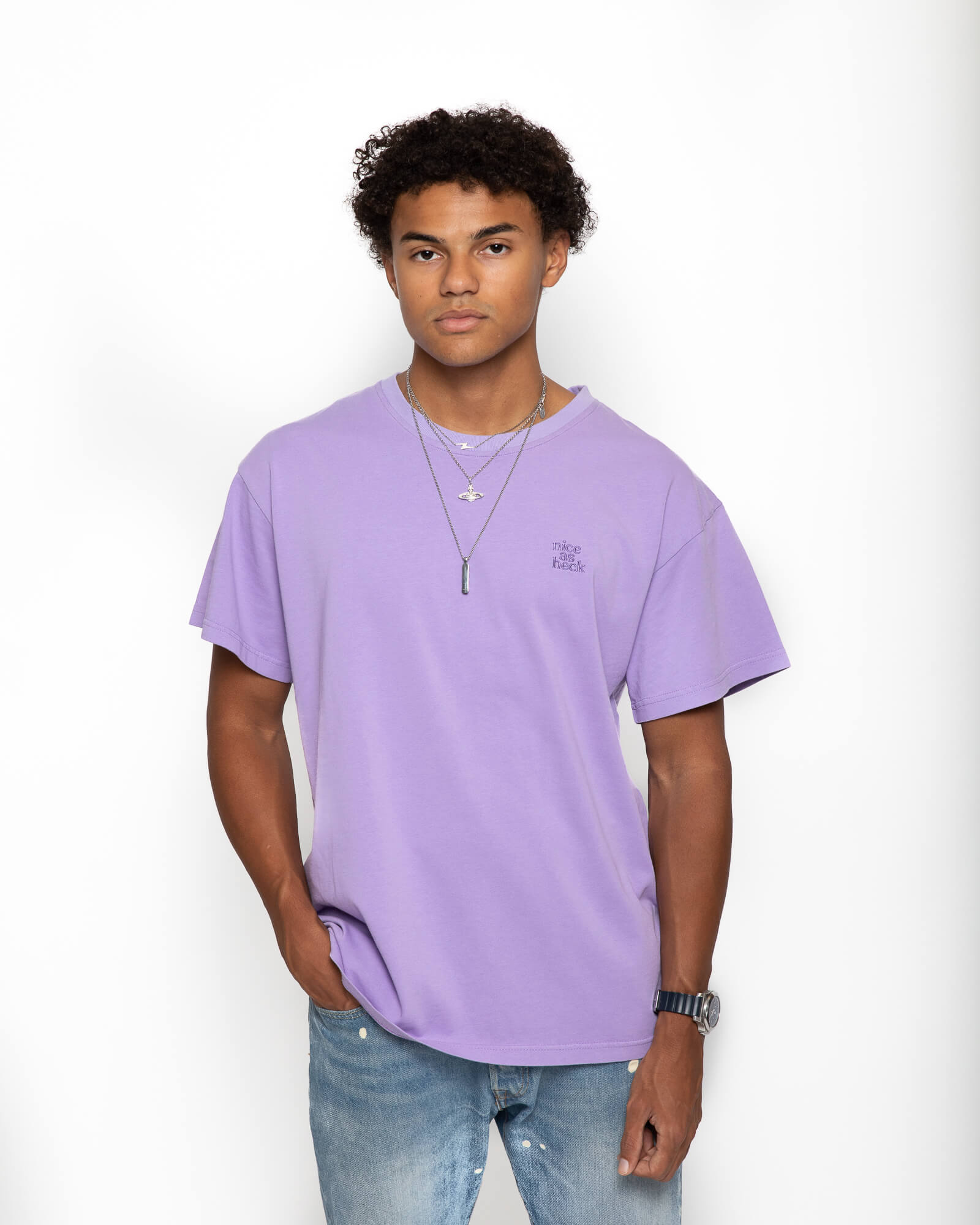 Male model wearing purple weekend tee with right hand in his pocket