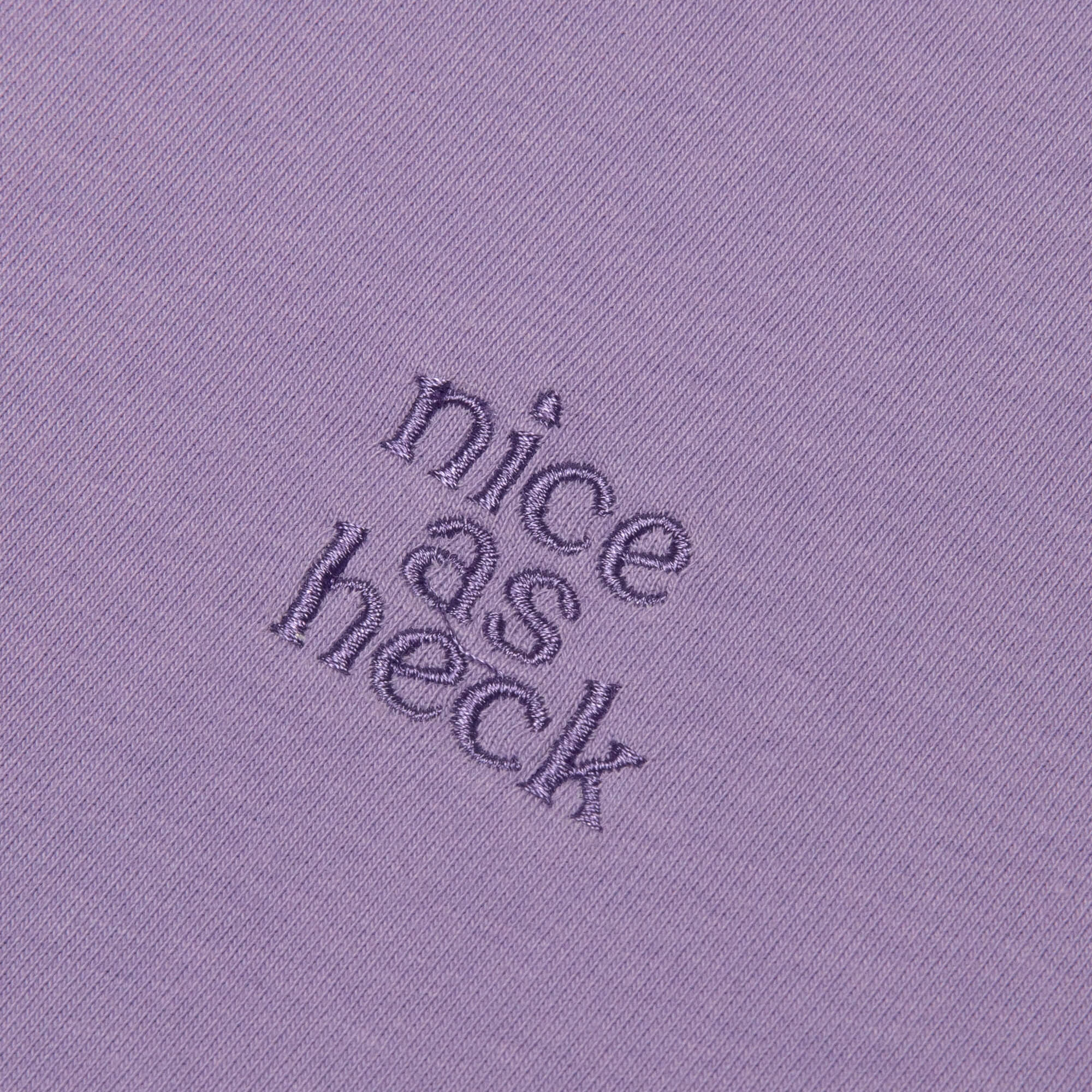 close up photo of the nice as heck logo on the purple weekender tee