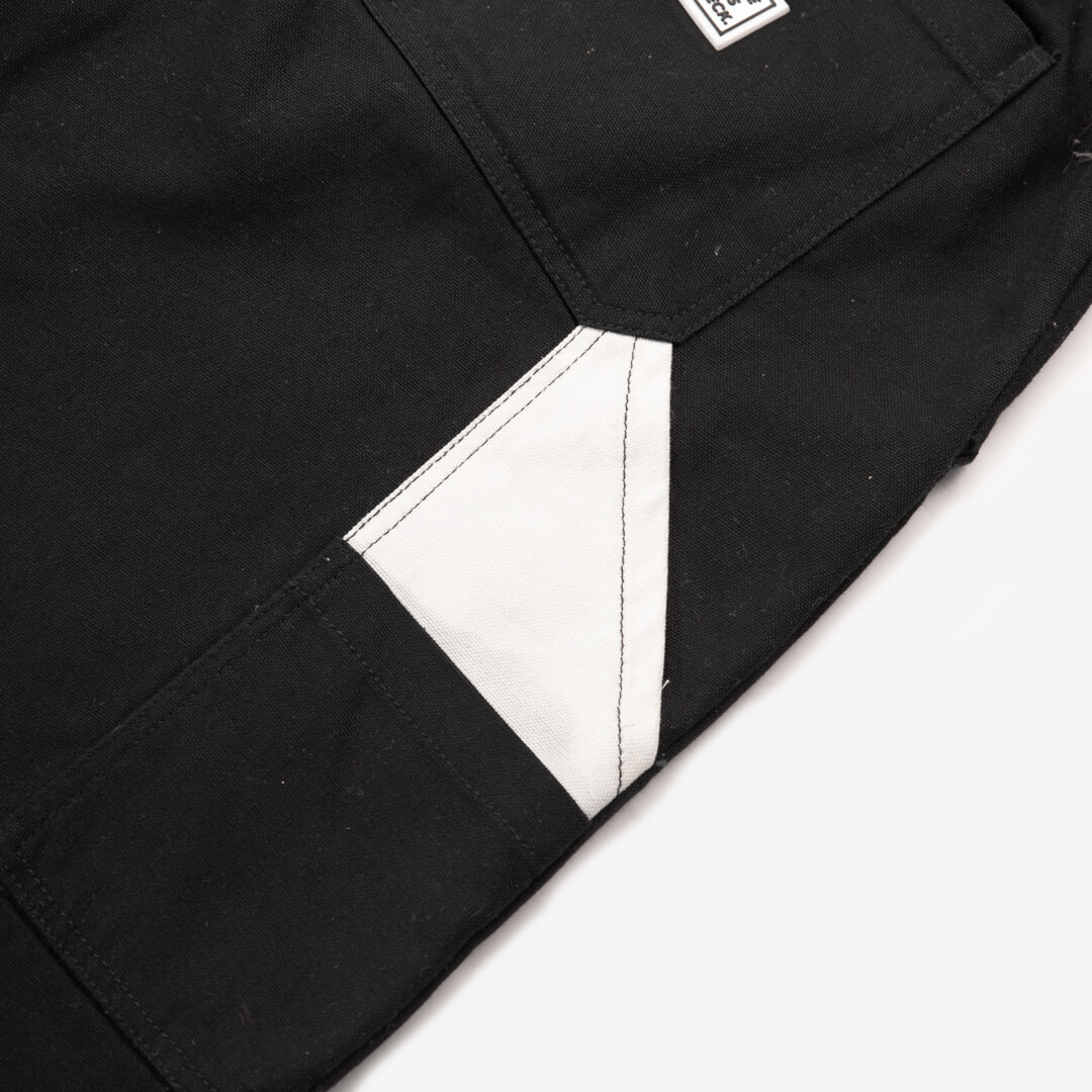 close up photo of the side pocket on the black cross country carpenter pants