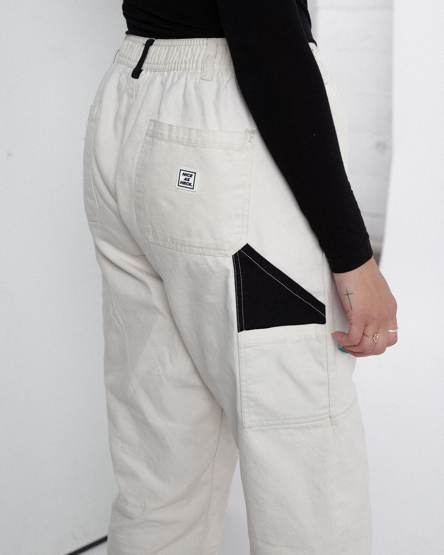 female model wearing off white cross country carpenter pants side view close up