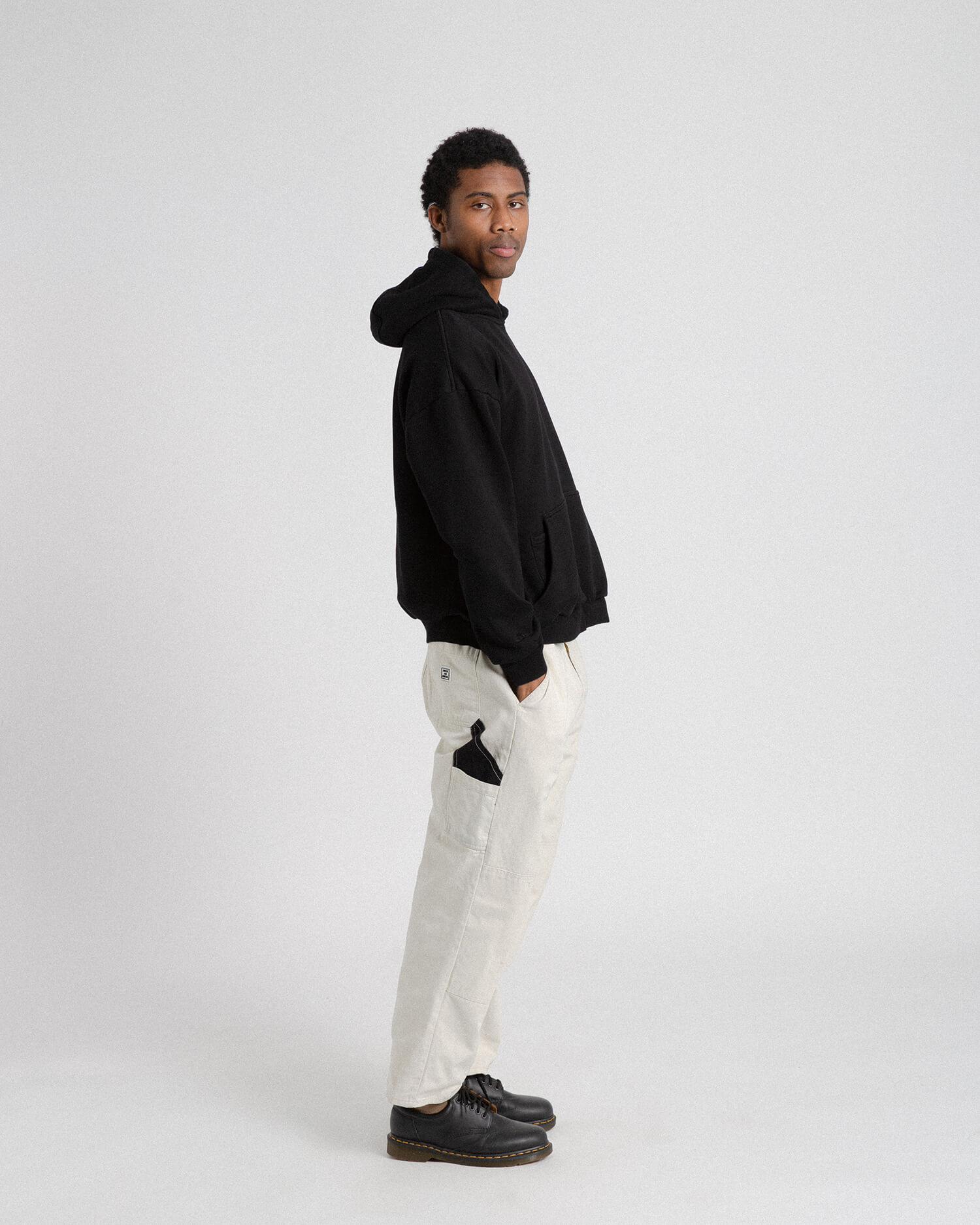 Male model wearing off white cross country carpenter pants side view