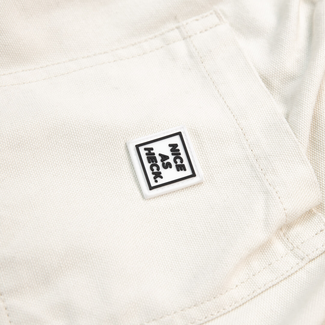 close up view of logo and backpocket on off white cross country carpenter pants
