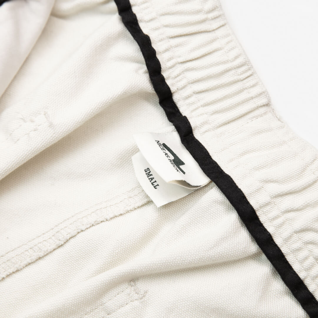close up view of waistline on off white cross country carpenter pants