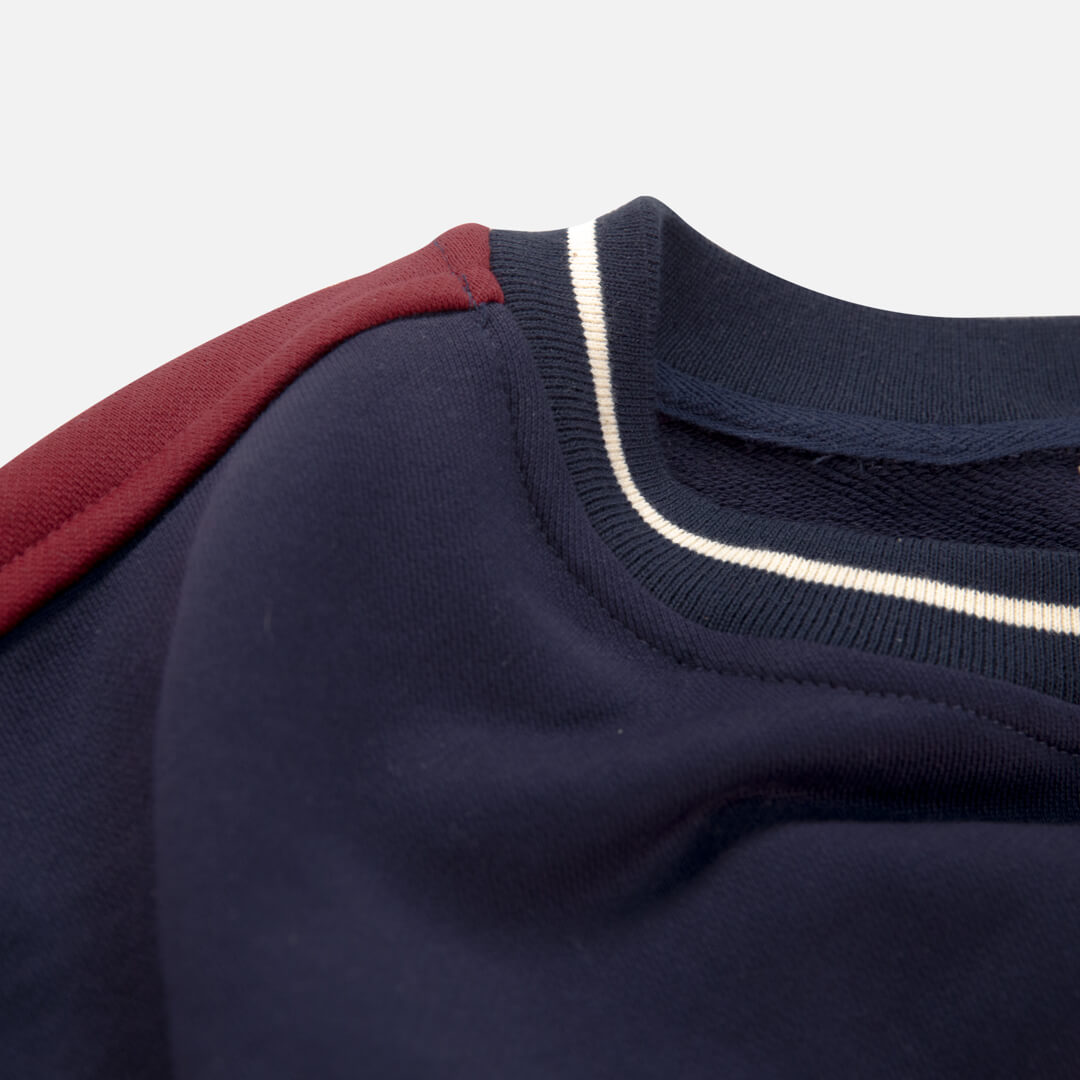 close up view of the navy campfire crewneck neckline and stripe on arm