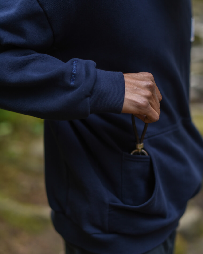 male model holding pocket of navy backcountry hoodie
