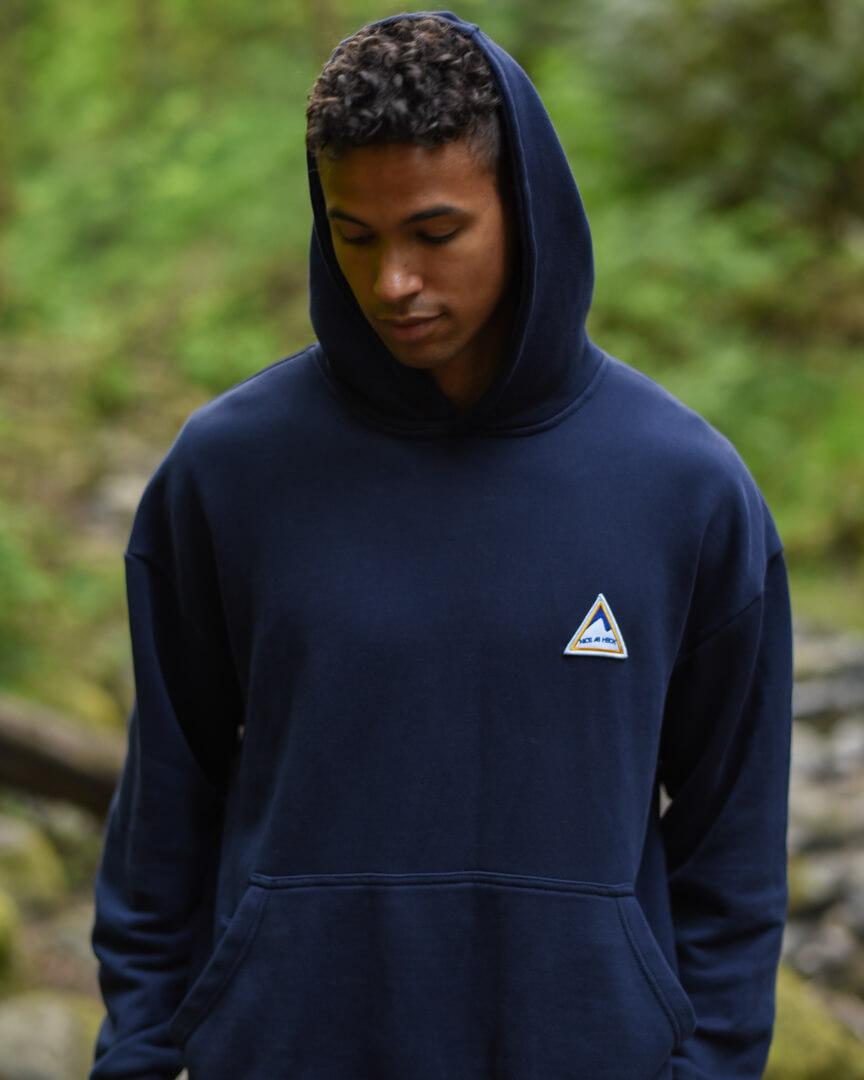 male model looking down wearing the navy backcountry hoodie