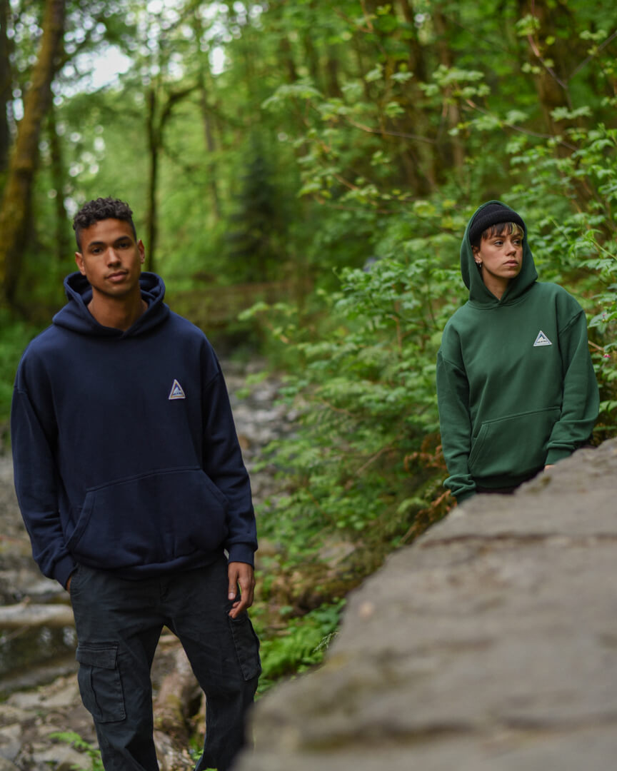 male model wearing the navy backcountry hoodie and female wearing the green hoodie