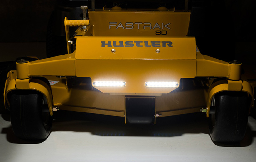 Image of the front of a yellow mower with lights mounted in the center and lit up