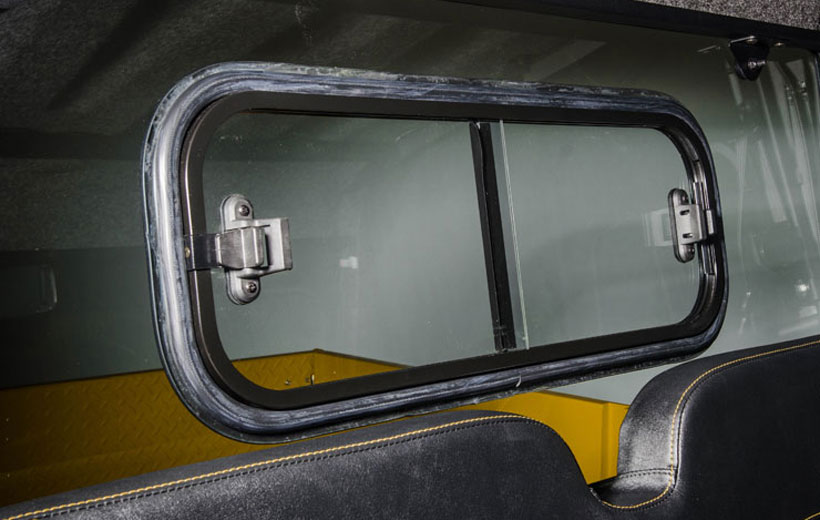 Image of a window with latches on either side in the back of a cab of a utility vehicle