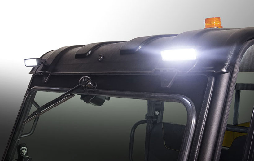 Image of the front roof line of a utility vehicle with lights that are turned on mounted on it.