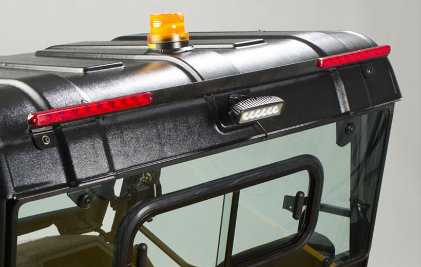 Image of the back roof line of a utility vehicle with red brakes lights and a center tail light mounted to it.