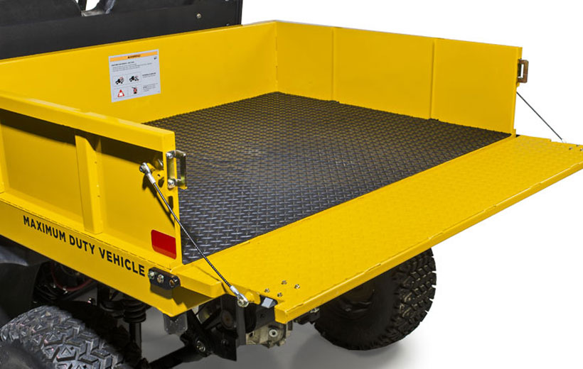 Image of the bed of a utility vehicle with the gate down and a black mat visible lining the bed.