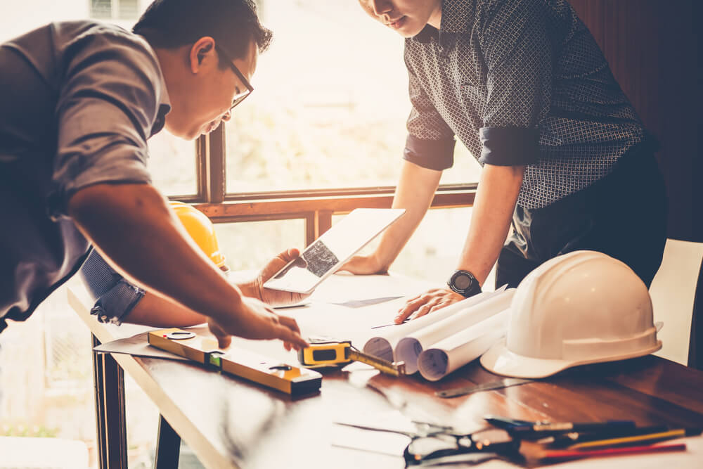 Engineers and businessmen are discussing construction projects in workplace.