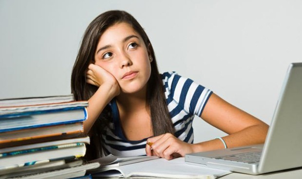 Garota de, aproximadamente, 15 anos, em um fundo cinza, sentada e apoiando seus braços em uma mesa de cor semelhante, a qual está cheia de livros, cadernos e um notebook. Ela está com um olhar distante, sem conseguir ter foco e atenção nos estudos.