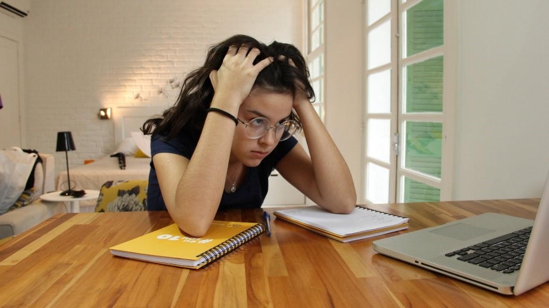 Menina de, aproximadamente, 15 anos, em seu quarto tentando estudar em uma mesa de madeira com os seus cadernos e notebook. Ela está frustrada por não estar entendendo o conteúdo da matéria.