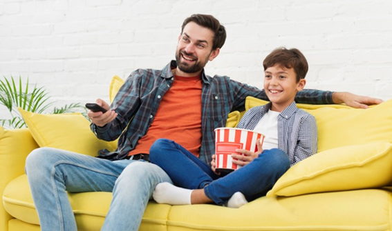 Pai e filho de, aproximadamente, 6 anos, sentados em um sofá amarelo. Eles estão assistindo um filme juntos após um dia com várias tarefas concluídas.