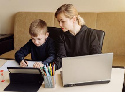Mãe interessada nos estudos do filho de, aproximadamente, 6 anos, enquanto ele faz o seu dever de casa. Ambos estão sentados em uma mesa branca com folhas, lápis, tablet e computador para pesquisas, em sua superfície.